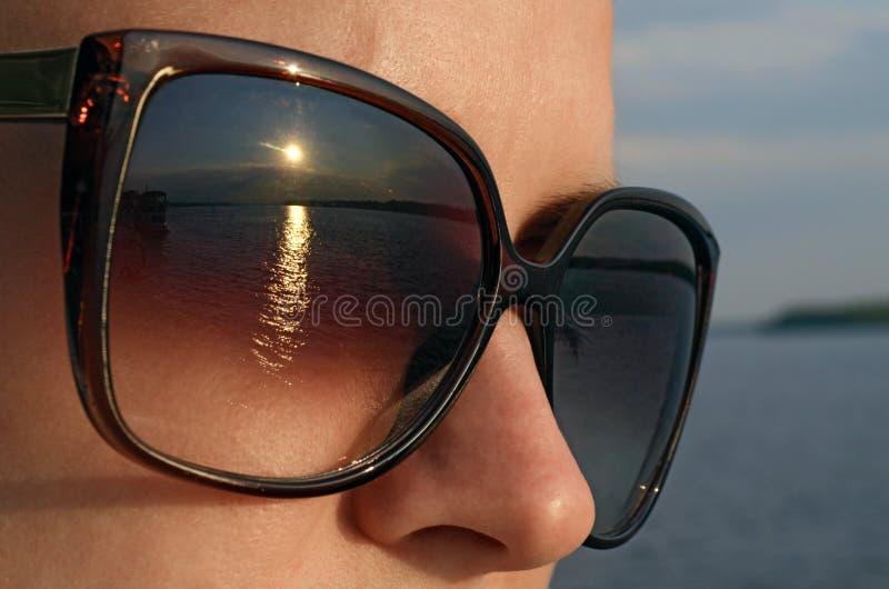 A jovem mulher nos óculos de sol olha o sol na praia fotografia de stock royalty free