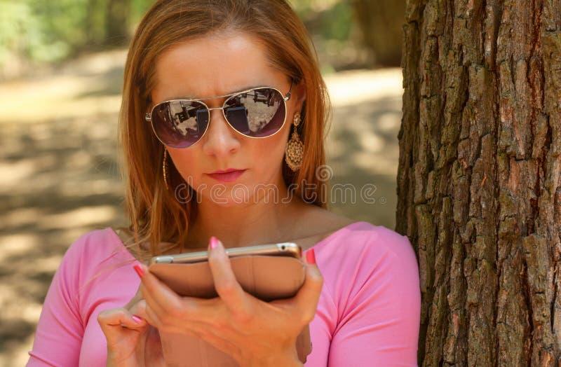 Jovem mulher nos óculos de sol, sentando-se em um banco no parque, w de trabalho imagens de stock royalty free