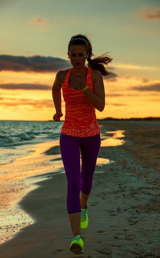 A jovem mulher nos esportes alinha na praia em movimentar-se do por do sol fotos de stock royalty free
