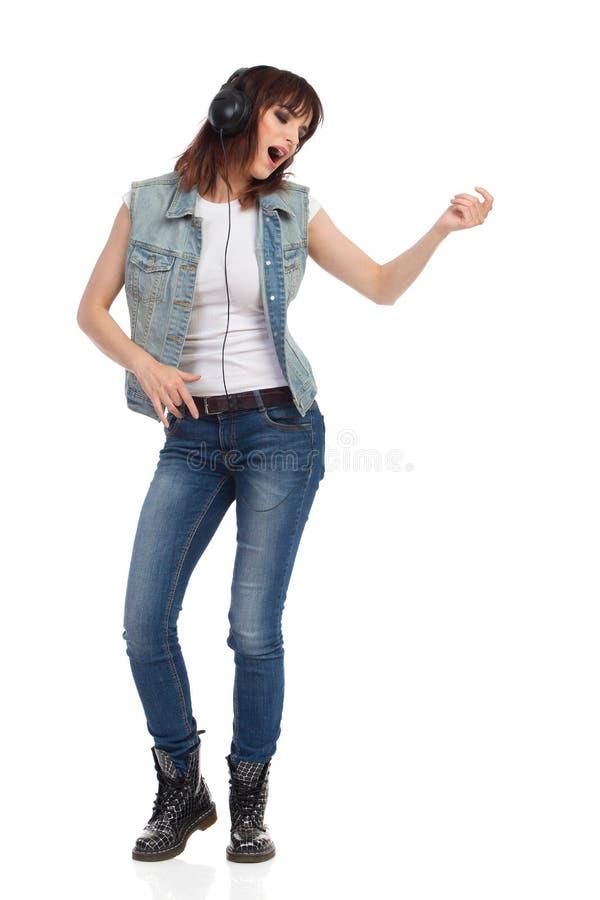 A jovem mulher nos fones de ouvido é de canto e de jogo Air Guitar foto de stock royalty free