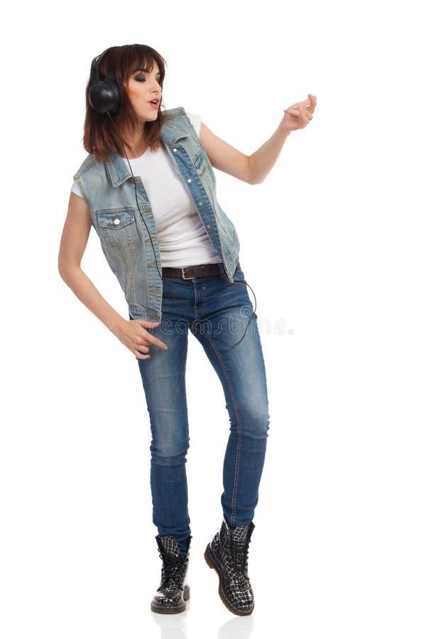 A jovem mulher nos fones de ouvido é de canto e de jogo Air Guitar fotos de stock royalty free