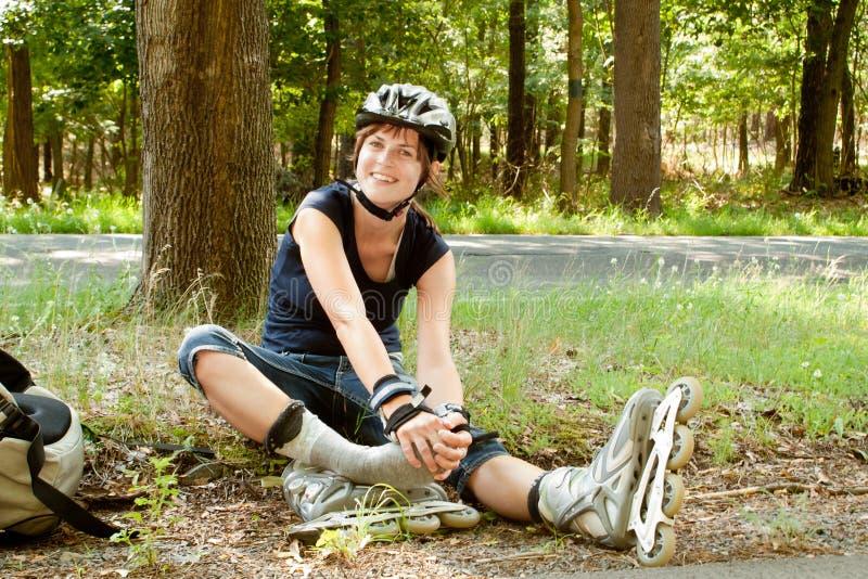 Jovem mulher nos patins de rolo que sentam-se guardando o pé foto de stock royalty free