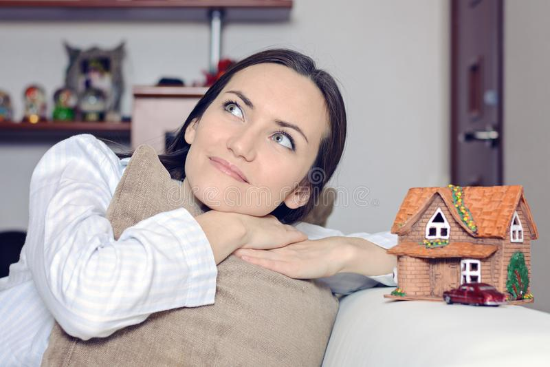 Jovem mulher nos pijamas que encontram-se em um sofá branco em uma sala na frente de uma casa de Wendy e um carro, e sonhos de um imagem de stock royalty free