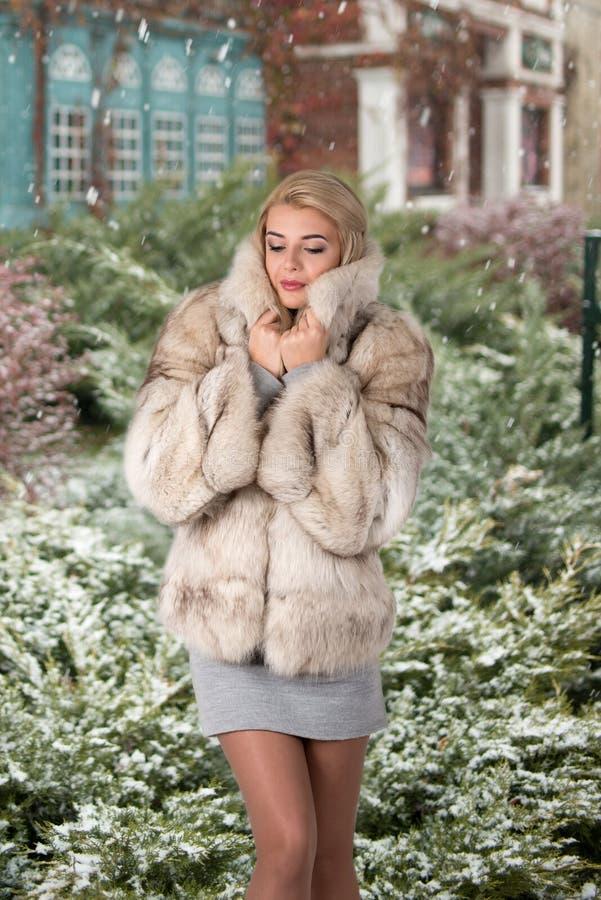 A jovem mulher o louro em standts curtos de um casaco de pele no s imagem de stock