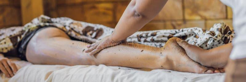 A jovem mulher obtém esfrega a massagem na BANDEIRA do salão de beleza dos termas, FORMATO LONGO fotografia de stock