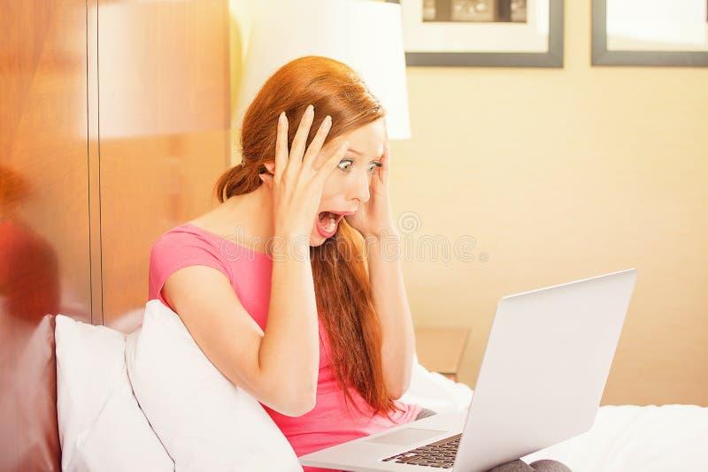 Jovem mulher ocasional engraçada chocada que usa o portátil fotos de stock royalty free