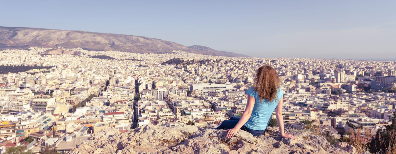 A jovem mulher olha a arquitetura da cidade de Atenas, Gr?cia fotografia de stock royalty free