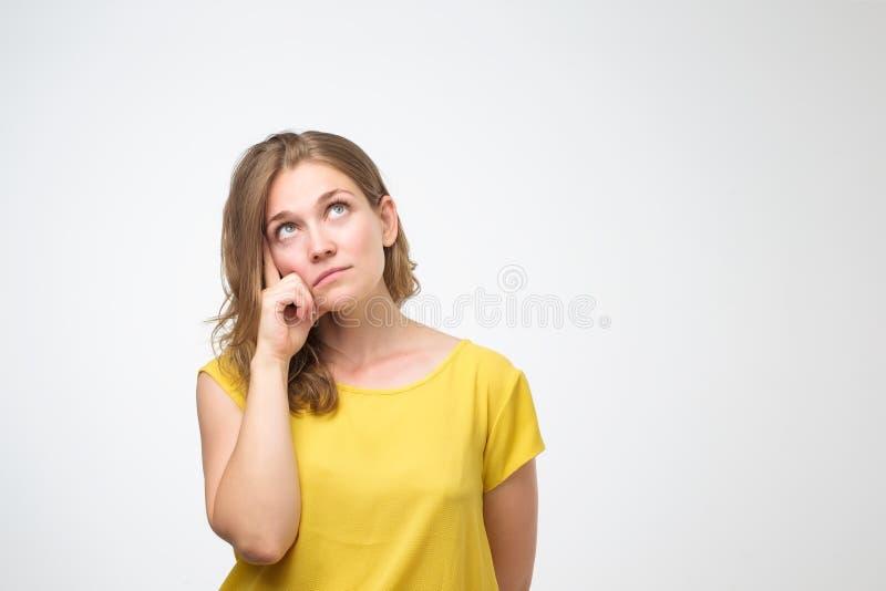 A jovem mulher olha com dúvida veste a camisa amarela de t, tentando fazer a decisão direita imagem de stock royalty free