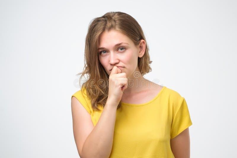 A jovem mulher olha com dúvida veste a camisa amarela de t, tentando fazer a decisão direita fotografia de stock royalty free