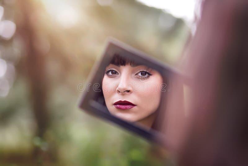 A jovem mulher olha em seu espelho imagem de stock