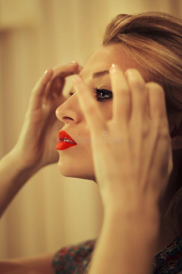 A jovem mulher olha no espelho foto de stock