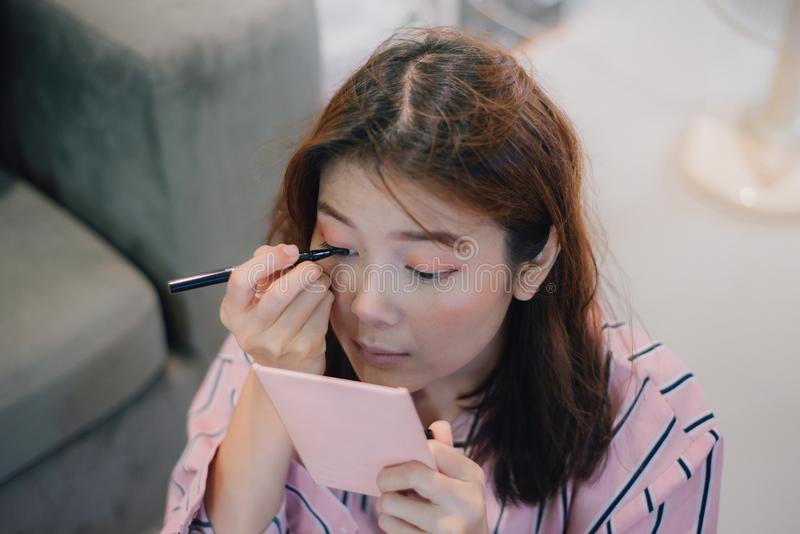A jovem mulher olha no espelho cor-de-rosa do bolso e em pôr a cor do lápis do olho sobre os olhos fotografia de stock royalty free