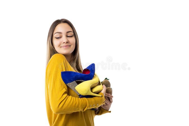 Jovem mulher orgulhosa bonita que guarda muitas sapatas sobre o fundo branco imagem de stock