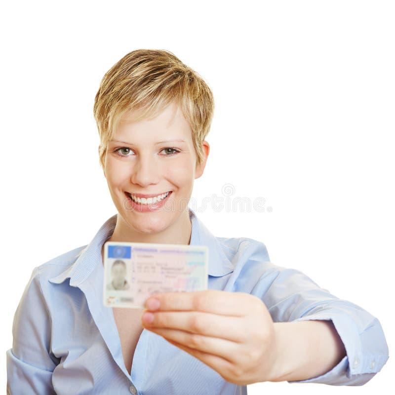 Jovem mulher orgulhosa com a licença de motoristas nova imagem de stock