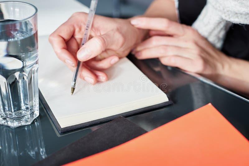 Jovem mulher ou estudante que trabalham e que escrevem no caderno do papel, usando o telefone esperto Perto acima das mãos da mul foto de stock