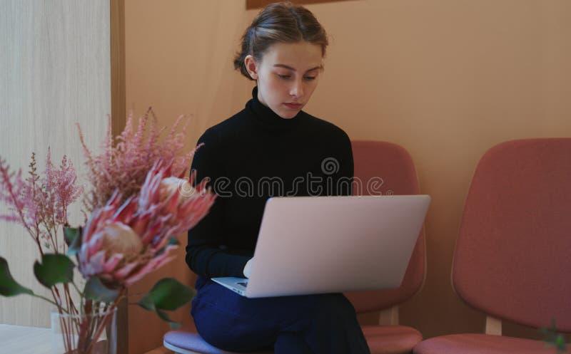 Jovem mulher ou estudante que trabalham e que escrevem usando o portátil em joelhos Sentando-se no café perto da janela, humor ro foto de stock