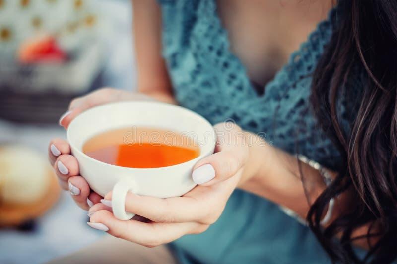Jovem mulher ou menina no copo azul da posse do vestido do chá nas mãos fotografia de stock