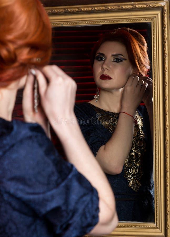A jovem mulher põe sobre brincos bonitos na frente do espelho Menina bonita no estilo do vintage imagem de stock