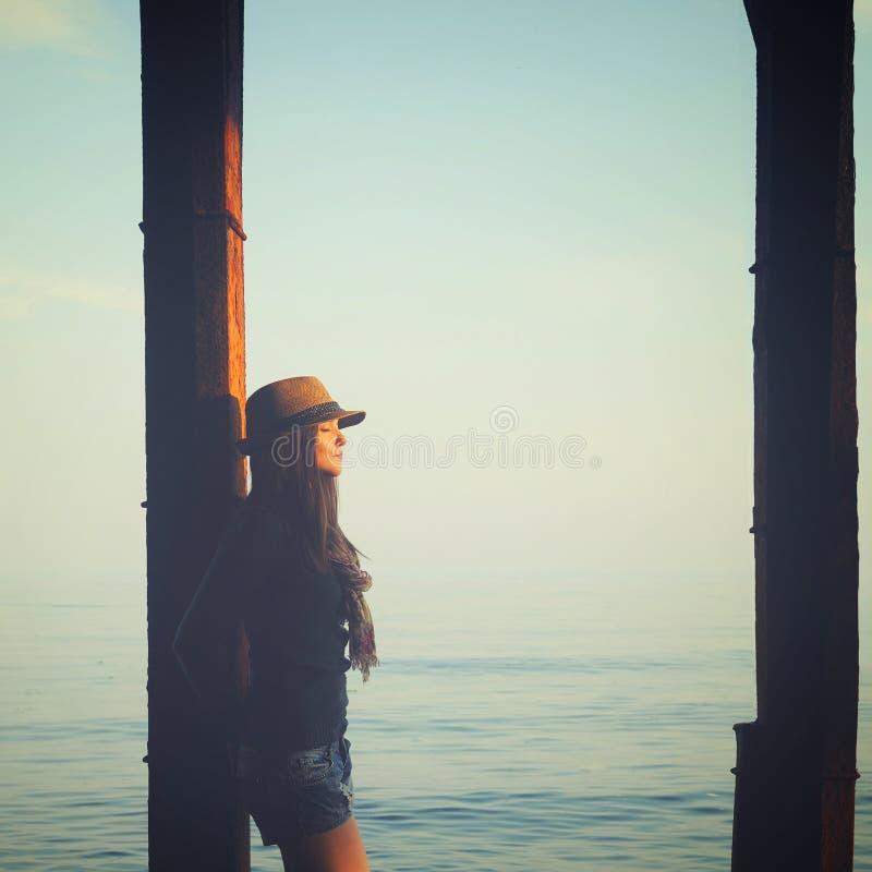 Jovem mulher parada debaixo do píer em uma água do mar, desfrute da luz do sol do outono imagem de stock royalty free