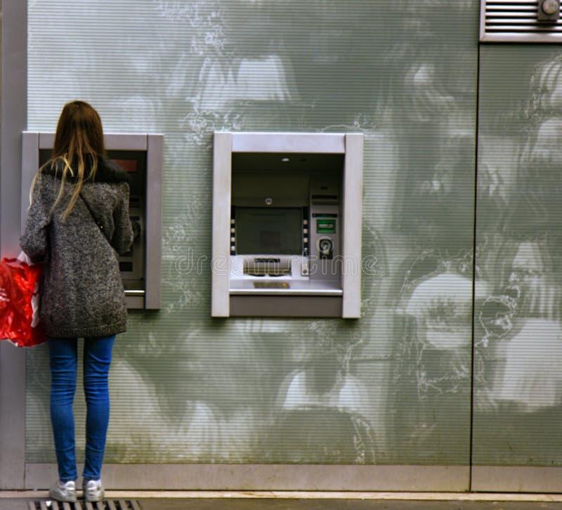 A jovem mulher parisiense faz a transação monetária na rua ATM fotos de stock