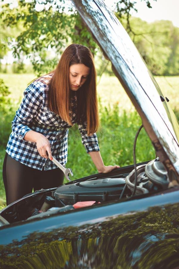 A jovem mulher pela borda da estrada após seu carro dividiu Imagem tonificada foto de stock
