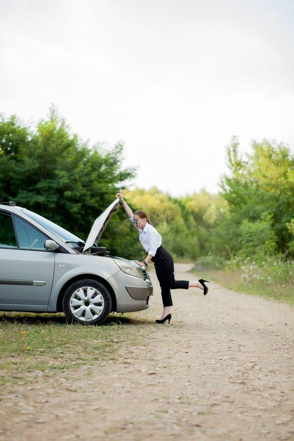 A jovem mulher pela borda da estrada depois que seu carro a tem dividido abriu a capa para ver o dano imagens de stock royalty free