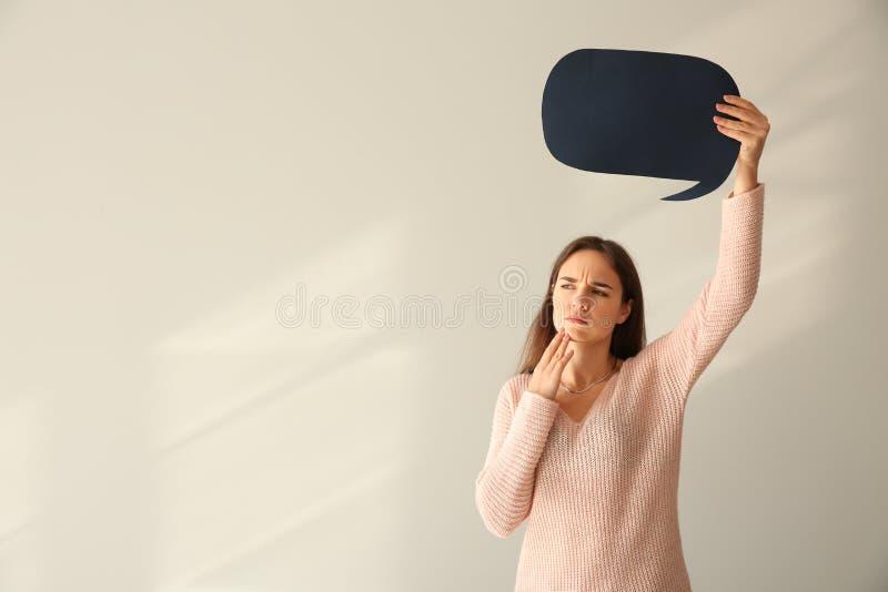 Jovem mulher pensativa com bolha vazia do discurso no fundo claro foto de stock royalty free