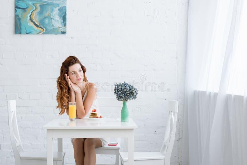 jovem mulher pensativa com suco de laranja e panquecas com a morango para o café da manhã fotos de stock