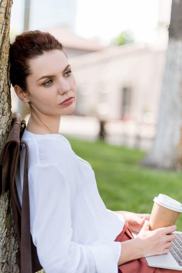 jovem mulher pensativa com a xícara de café do portátil e do papel que inclina-se para trás no tronco de árvore no parque imagens de stock royalty free