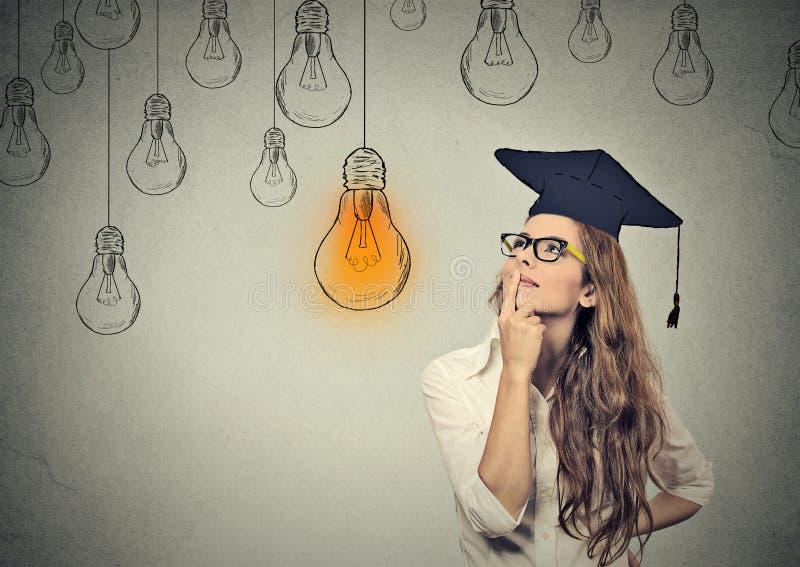 Jovem mulher pensativa do aluno diplomado no tampão que olha a ampola brilhante imagens de stock