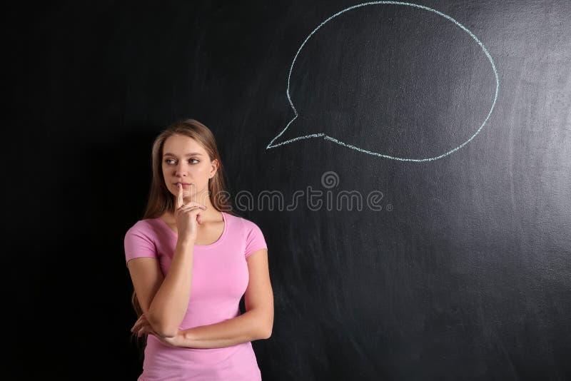 Jovem mulher pensativa e bolha vazia do discurso tiradas no quadro-negro imagens de stock