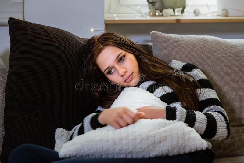 Jovem mulher pensativa e só que relaxa em um sofá fotografia de stock royalty free