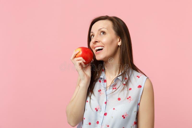 Jovem mulher pensativa na roupa do verão que olha acima, mantendo o fruto vermelho maduro fresco da maçã isolado no fundo pastel  foto de stock royalty free