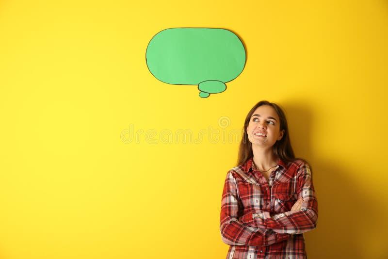 Jovem mulher pensativa perto da bolha vazia do discurso no fundo da cor imagem de stock royalty free