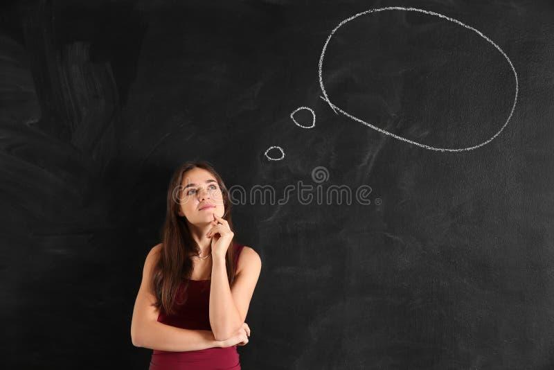 Jovem mulher pensativa perto da bolha vazia do discurso tirada no quadro-negro imagem de stock