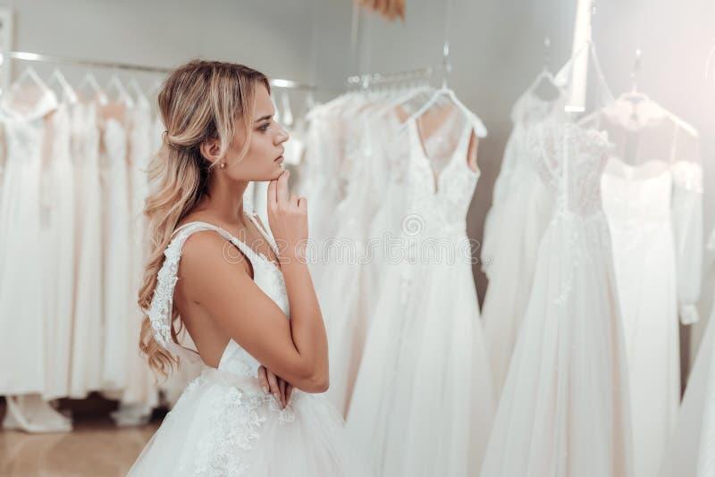 Jovem mulher pensativa que escolhe seu vestido de casamento fotos de stock