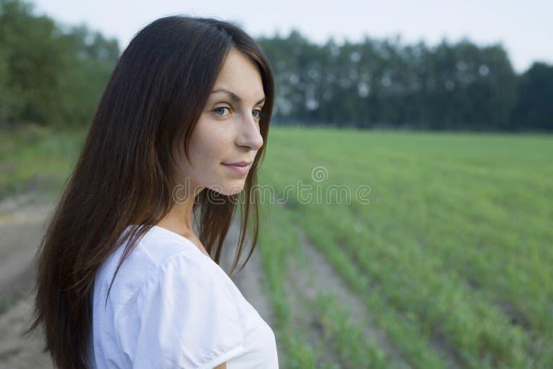 Jovem mulher pensativa que está no campo imagem de stock
