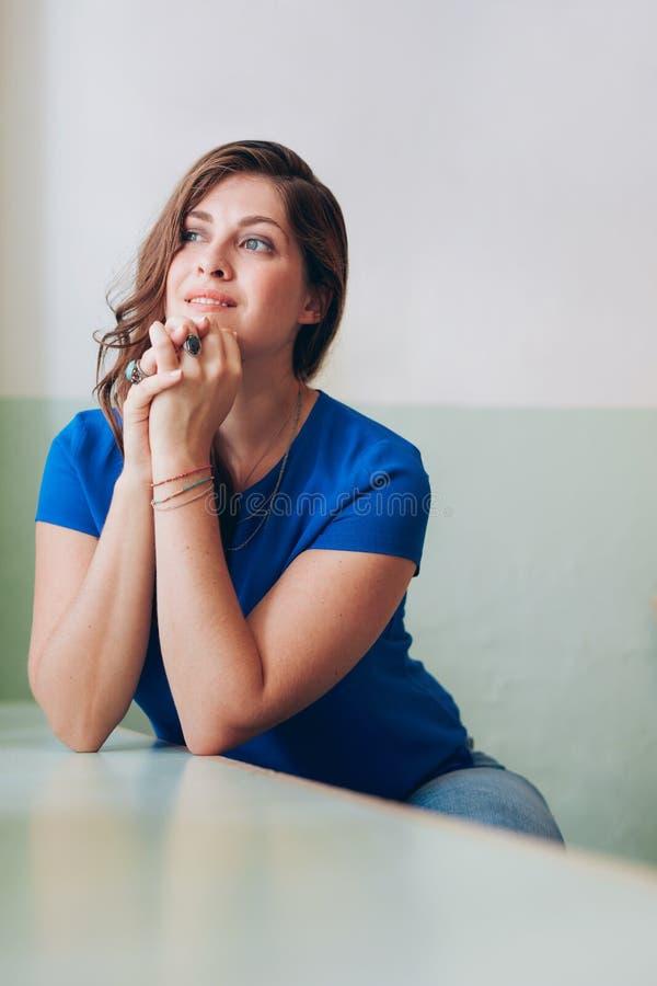 Jovem mulher pensativa que senta-se em uma tabela imagens de stock royalty free