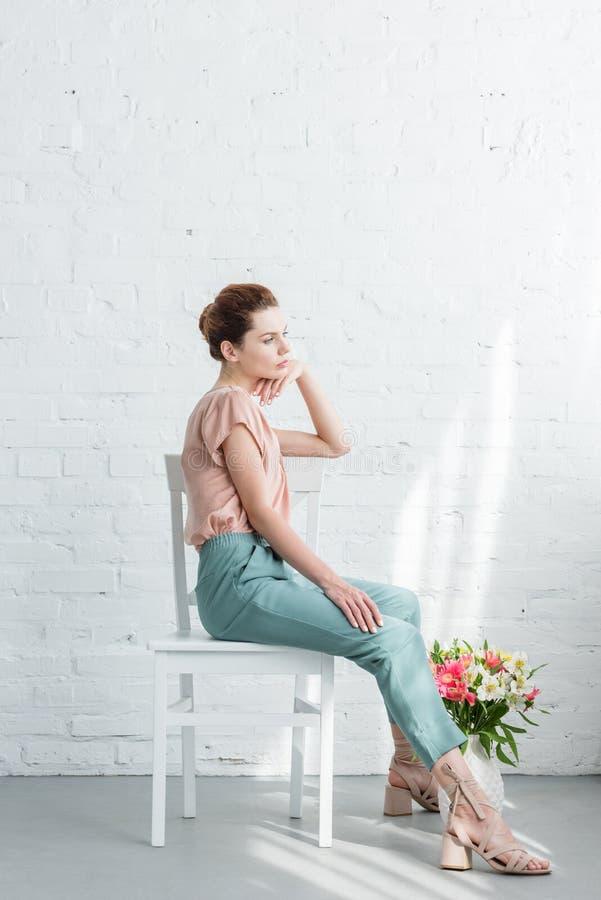 jovem mulher pensativa que senta-se na cadeira com as flores no assoalho na frente do branco imagem de stock