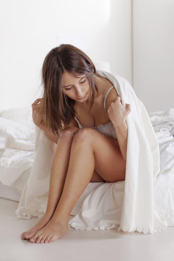 Jovem mulher pensativa que senta-se na cama branca. imagens de stock