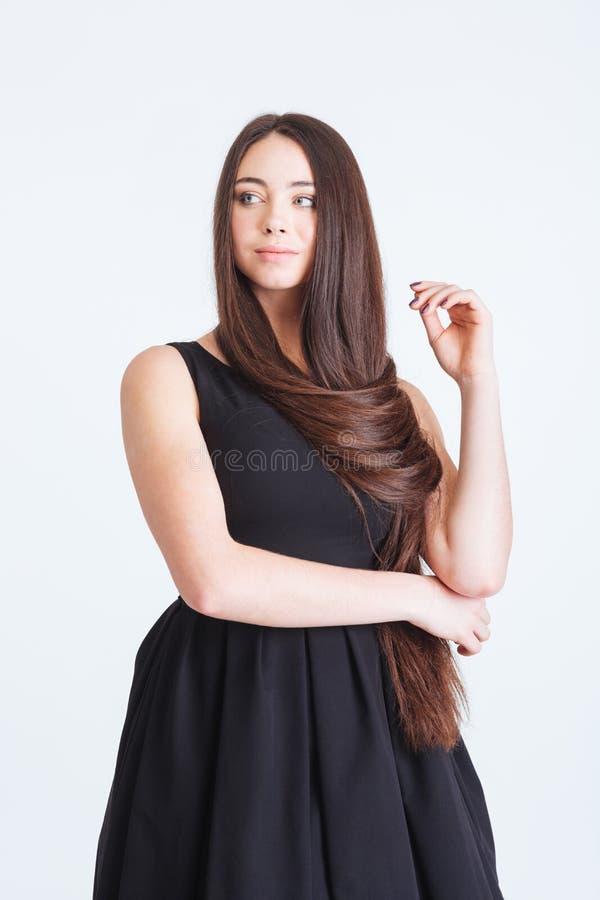 Jovem mulher pensativa segura com cabelo escuro longo bonito fotos de stock