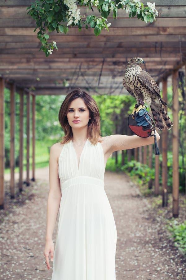 Jovem mulher perfeita com o pássaro no parque da mola exterior fotografia de stock
