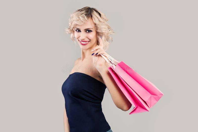 Jovem mulher perfeita que guarda sacos de compras no fundo cinzento imagens de stock