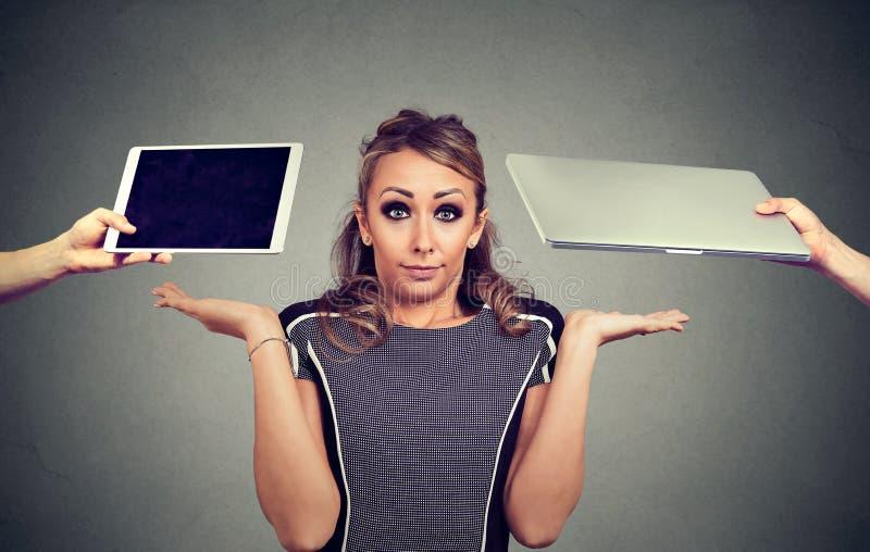 Jovem mulher perplexo que shrugging os ombros incertos que escolher a tabuleta ou o laptop fotos de stock royalty free