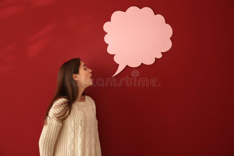 Jovem mulher perto da bolha vazia do discurso no fundo da cor fotos de stock royalty free