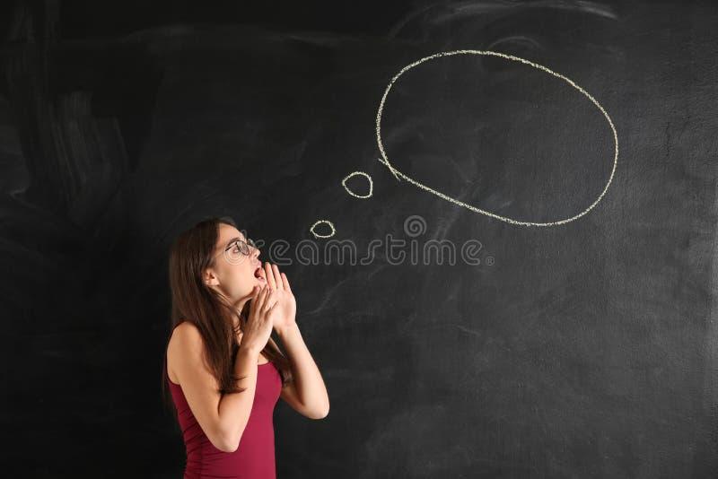 Jovem mulher perto da bolha vazia do discurso tirada no quadro-negro foto de stock royalty free