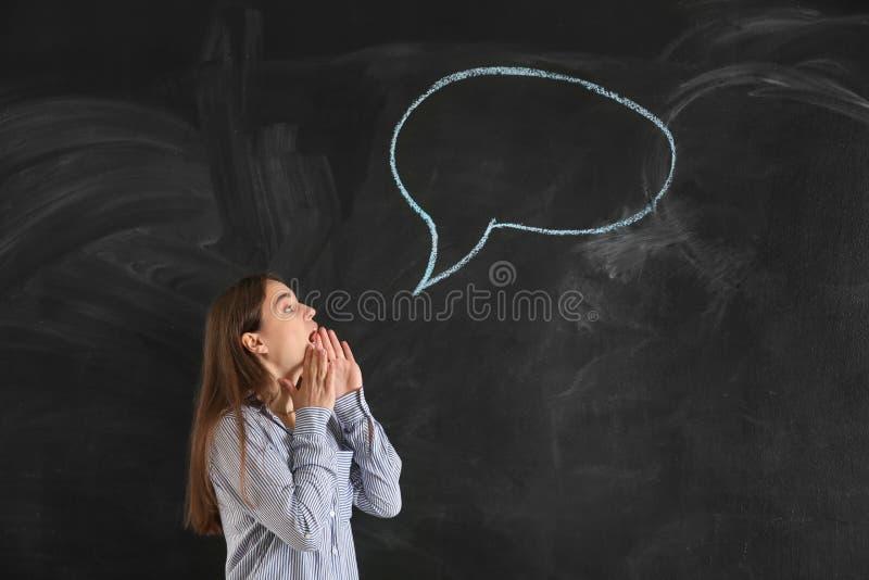 Jovem mulher perto da bolha vazia do discurso tirada no quadro-negro fotos de stock