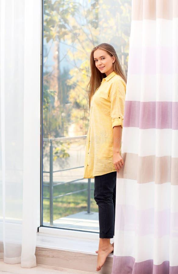 Jovem mulher perto da janela com cortinas abertas fotos de stock royalty free
