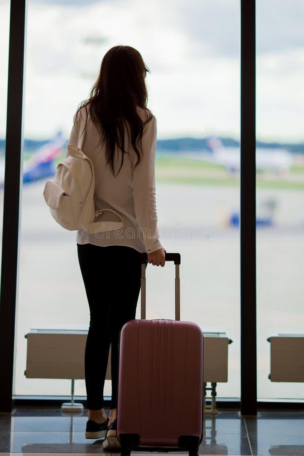 Jovem mulher perto da janela em um avião de espera do voo da sala de estar do aeroporto imagem de stock royalty free