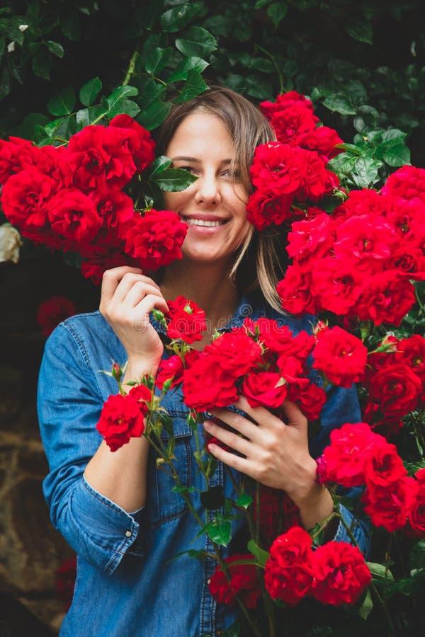 Jovem mulher perto do arbusto de rosas vermelhas em um jardim foto de stock royalty free